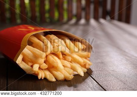 Mykolaiv, Ukraine - August 12, 2021: Big Portion Of Mcdonald's French Fries On Wooden Table, Closeup
