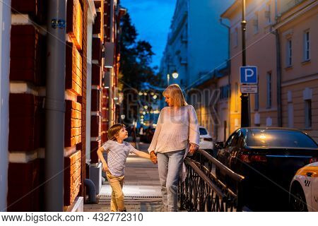 Mother And Son Walking In The City Center Street. Mom And Kid Taking A Summer Evening Walk Outside I