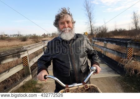 Smiling senior man with a beard on a bike path riding his bicycle
