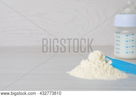 Powdered Infant Formula, Scoop And Feeding Bottle On White Wooden Table, Space For Text. Baby Milk