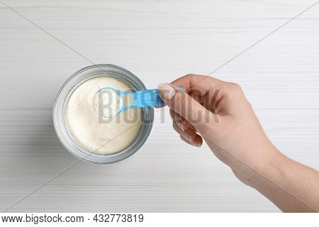 Woman Taking Powdered Infant Formula With Scoop From Can At White Wooden Table, Top View