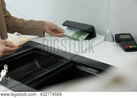 Cashier Checking Money With Detector At Currency Exchange Department In Bank, Closeup
