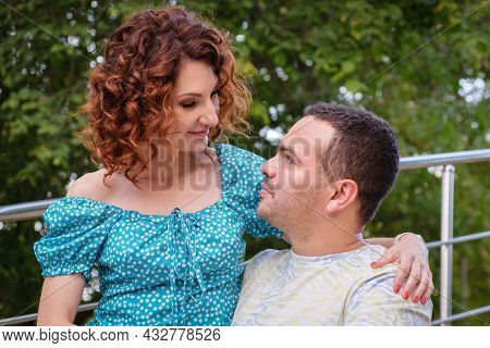 Loving Couple On A Park Look At Each Other With Tenderness. Man In A T-shirt And A Curly Woman In Dr