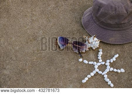 Brown Panama Hat, Sunglasses, Seashell And Sun Made Of Small White Pebbles Lie On Sand Beach Ocean S