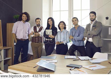 Team Of Happy Successful Business Professionals Standing By Window In Modern Office