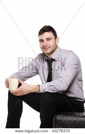 Business Man Sat Holding A Cup Of Coffee