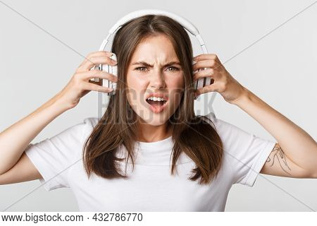 Close-up Of Angry And Confident Young Girl Complaining On Awful Music In Wireless Headphones, Grimac