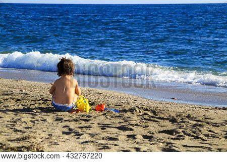 Baby Playing On The Sand Of The Salinas Beach In Cabo De Gata, Almeria, Spain