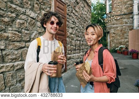 Happy young intercultural couple having fastfood with drinks in urban environment