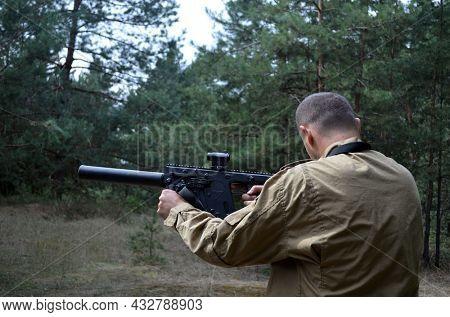Man with KRISS Vector 9*21 caliber submachine gun in the forest. Unformal shooting range near Kiev. September 6,2021. Kiev Region, Ukraine