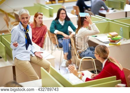 Female professor and students having good time at the lecture in a classroom