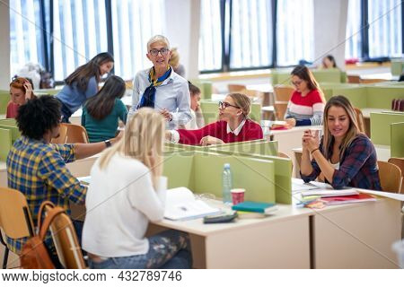 Female professor in a conversation with students at a lecture in a classroom