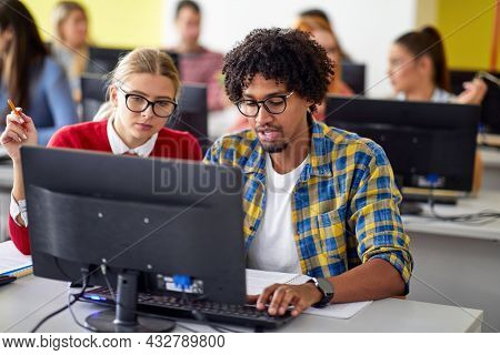 Students at the informatics lecture working together in the university computer classroom. Smart young people study at the college. Education, university, learning and multi ethnic people concept