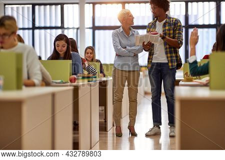 A male student in the university class room asking professor for a help about new lesson. Smart young people study at the college. Education, college, university, learning and multiethnic people