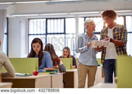Female professor likes helping students at a lecture in the university classroom