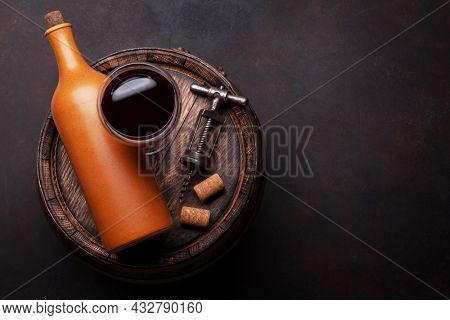 Wine bottle, vintage corkscrew and red wine glass on old wooden barrel. Top view flat lay with copy space