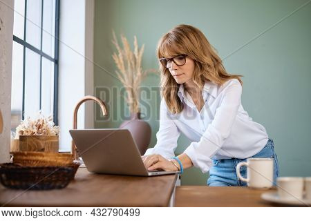 Shot Of A Middle Aged Woman Using A Laptop And Having Video Conference While Standing In The Kitchen