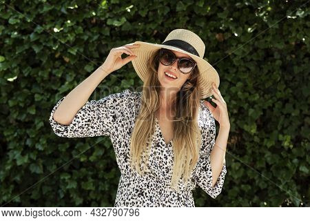 Attractive Young Woman Portrait While Wearing Sunglasses And Straw Hat And Standing Outdoor