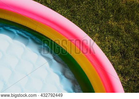 A Multicolored Childrens Inflatable Pool Stands On The Green Grass In Summer