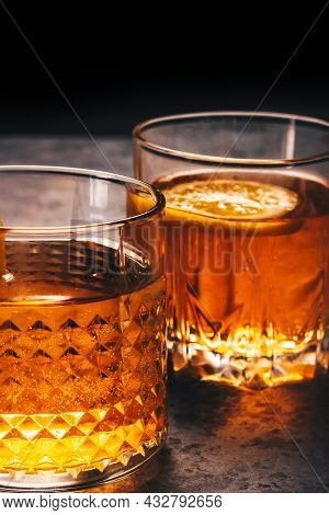 Alcohol Drink In Two Rock Glasses. Scotch Whiskey, Rum, Bourbon, Liquor, Or Brandy Cocktails On The