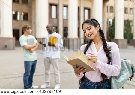Happy University Student Girl Holding Book, Standing Outdoors At University Campus With Her Classmat