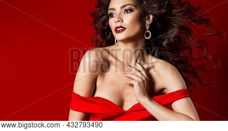 Sensual Fashion Model Portrait In Red Dress. Woman Beauty Perfect Face Make Up And Long Curly Hair F