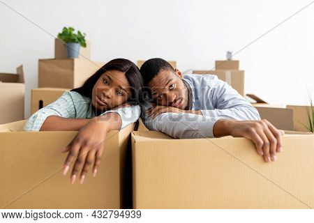 Moving Stress Concept. Exhausted Black Family Leaning On Unpacked Boxes, Having Problems During Relo