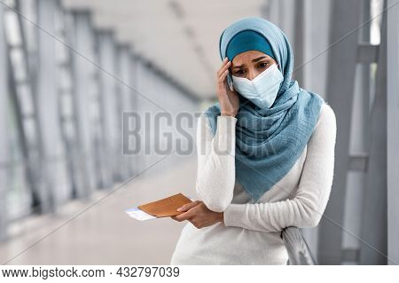 Cancelled Flight. Depressed Islamic Woman In Mask And Hijab Standing In Airport