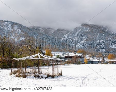 Russian Village Chemal In The Snow. View Of The Snow-capped Altai Mountains And Clouds. Chemal, Alta