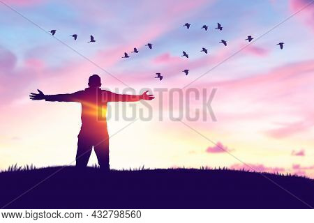 Man Rising Hands And Birds Flying On Sunset Sky At Nature Field Abstract Background. Freedom Feel Go