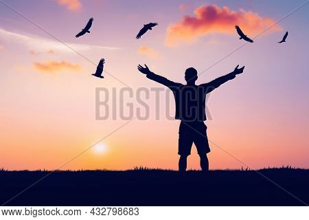 Man Rising Hands And Eagle Birds Flying On Sunset Sky At Nature Field Abstract Background. Freedom F