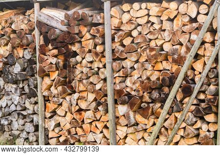 Prepared For The Winter A Mixture Of Firewood From Different Species Of Trees, Neatly Stacked In A P
