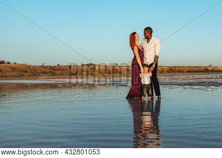 Happy Mixed Race Family At The Beach On Beautiful Summer Day. Outdoors Portrait Of Young Multiethnic