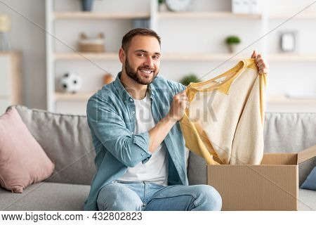 Satisfied Male Client Taking Out New Sweater From Cardboard Box, Happy With Delivery Service At Home