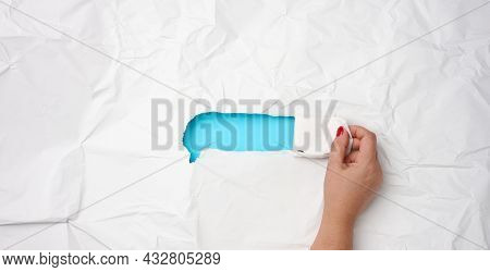 Female Hand Tears Off A Strip From White Crumpled Paper, Place For An Inscription