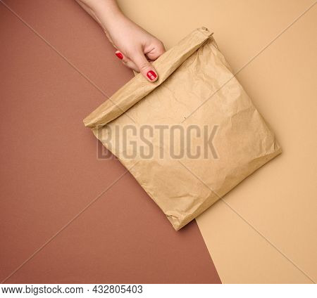 Hand Holding A Full Paper Bag Of Brown Kraft Paper Ona Brown Background, Close Up
