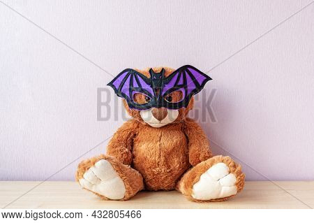 Funny Brown Teddy Bear With Purple Bat Shaped Mask Sits On Wooden Table By Light Pink Wall In Room.