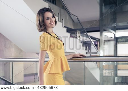 Young fashion business woman leaning on railing at office Stylish female model with bob hairstyle in yellow peplum dress