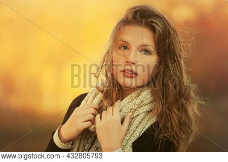 Young fashion girl in black pullover and white knitted scarf walking outdoor