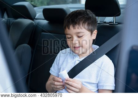 Cinematic Portrait Mixed Race Boy Siting In Safety Car Seat Reading On Paper With Smiling Face,child