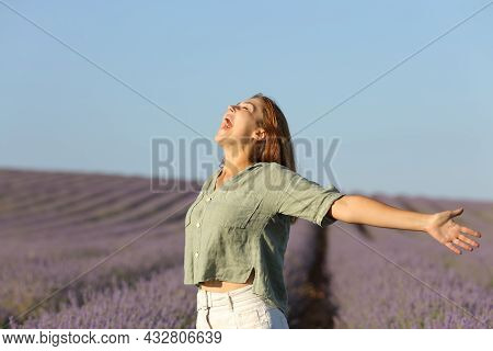 Happy Woman Outstretching Arms And Screaming Standing In A Lavender Field