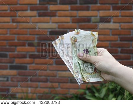 Hand Of A Woman Holding Peruvian Banknotes And Background With A Brick Wall