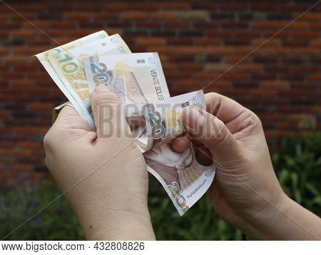 Hand Of A Woman Holding Peruvian Banknotes Outside A House