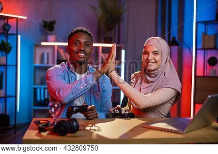 Cheerful Black Guy Giving High Five To Arabian Woman In Hijab While Sitting At Table With Laptop And