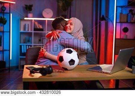 Happy Arabian Woman In Hijab Hugging With African American Man While Watching Football Game On Lapto
