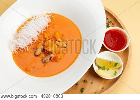 Traditional Soup Tom Yam. In A Plate On A Light Background. Selective Focus.