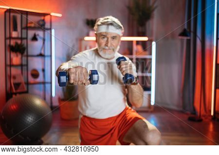 Blurred View Of Bearded Aged Man Having Evening Workout With Dumbbells At Home. Active Pensioner Spe