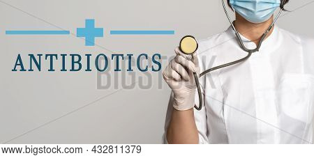 Antibiotics - Concept Of Text On Gray Background. Nearby Is A Cropped View Of Doctor In White Coat,