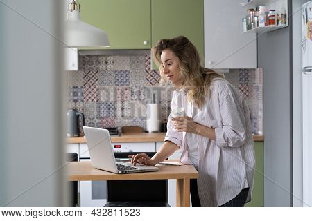 Businesswoman Or Remote Manager Work From Home In Morning Check Email On Laptop While Cooking Breakf