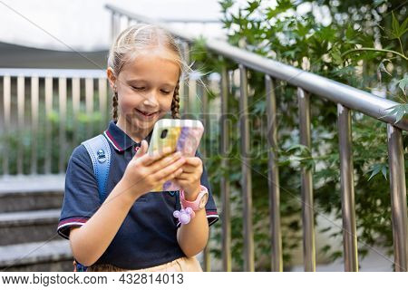 Little Caucasian Girl Is Playing With Mobile Phone In New Pop It Toy Case. Development Of Fine Motor